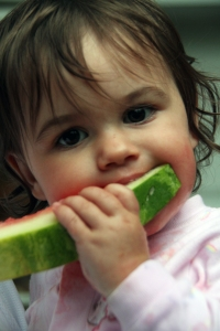 Kaitlyn enjoying her fourth piece of watermelon.