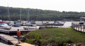 Rick walks to the dinghy at the Gore Bay Marina with some of our purchases while Guinevere sits in the bay.